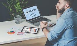 Ο νέος γενειοφόρος επιχειρηματίας κάθεται στο γραφείο στον πίνακα, lap-top με τη στατιστική ανάλυση επιγραφής στην οθόνη Στοκ εικόνες με δικαίωμα ελεύθερης χρήσης