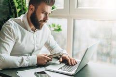 Ο νέος γενειοφόρος επιχειρηματίας στο άσπρο πουκάμισο κάθεται στον πίνακα και εργάζεται στο lap-top Το Freelancer λειτουργεί στο  Στοκ Εικόνες