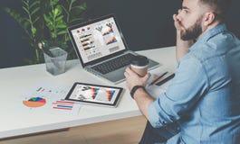 Ο νέος γενειοφόρος επιχειρηματίας στο πουκάμισο τζιν κάθεται στο γραφείο στον πίνακα, που μιλά στον κινητό καφέ τηλεφώνων και κατ Στοκ φωτογραφία με δικαίωμα ελεύθερης χρήσης