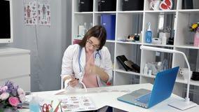 Ο νέος γιατρός γυναικών κάθεται στο γραφείο της και ανακτά τα αποτελέσματα της δοκιμής φιλμ μικρού μήκους