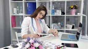 Ο νέος γιατρός γυναικών κάθεται στο γραφείο της και ανακτά τα αποτελέσματα της δοκιμής απόθεμα βίντεο