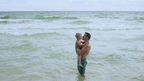Ο νέος γοητευτικός πατέρας έχει τη διασκέδαση με τον ευτυχή γιο του στην όμορφη μόνη παραλία 4k φιλμ μικρού μήκους