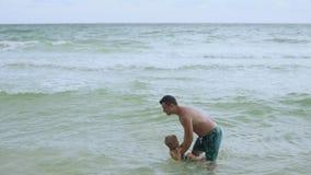 Ο νέος γοητευτικός πατέρας έχει τη διασκέδαση με τον ευτυχή γιο του στην όμορφη μόνη παραλία 4k απόθεμα βίντεο