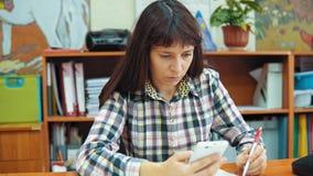 Ο νέος δάσκαλος γυναικών κάθεται στον πίνακα και εργάζεται με τα έγγραφα και ένα smartphone φιλμ μικρού μήκους