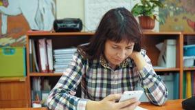 Ο νέος δάσκαλος γυναικών κάθεται στον πίνακα και εργάζεται με τα έγγραφα και ένα smartphone απόθεμα βίντεο
