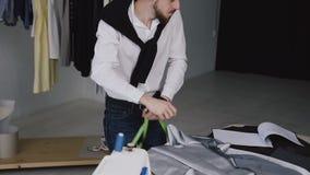 Ο νέος δημιουργικός σχεδιαστής των ενδυμάτων κάνει τις μετρήσεις ενός νέου προτύπου σακακιών και τις γράφει σε ένα σημειωματάριο  απόθεμα βίντεο
