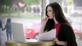 Ο νέος δημοσιογράφος γυναικών γράφει τα άρθρα, παίρνει τις σημειώσεις για χαρτί, εργάζεται σε ένα lap-top στα πλαίσια της οδικής  φιλμ μικρού μήκους