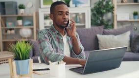 Ο νέος ειδικός αφροαμερικάνων μιλά στις επιχειρησιακές επαφές στο κινητό τηλέφωνο που γελά και που λειτουργεί με το lap-top απόθεμα βίντεο