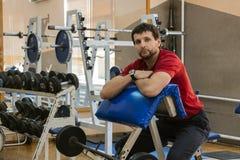 Ο νέος εκπαιδευτής σε μια απλή μικρή γυμναστική κάθεται στον πάγκο του Scott στοκ φωτογραφία