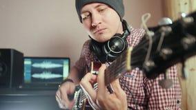 Ο νέος ελκυστικός αρσενικός μουσικός συνθέτει και καταγράφει την ηχητική λωρίδα παίζοντας την κιθάρα χρησιμοποιώντας τον υπολογισ απόθεμα βίντεο