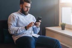 Ο νέος ελκυστικός γενειοφόρος επιχειρηματίας στο πουκάμισο και τα γυαλιά κάθεται στον καναπέ στο δωμάτιο και χρησιμοποιεί το smar Στοκ εικόνα με δικαίωμα ελεύθερης χρήσης