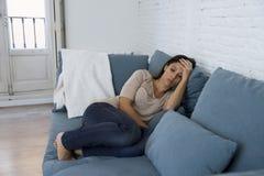 Ο νέος ελκυστικός λατινικός καναπές γυναικών στο σπίτι ανησύχησε να υποστεί την κατάθλιψη αισθαμένος λυπημένος και απελπισμένος Στοκ φωτογραφία με δικαίωμα ελεύθερης χρήσης