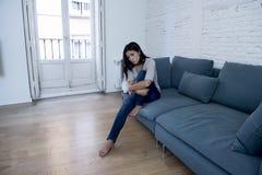 Ο νέος ελκυστικός λατινικός καναπές γυναικών στο σπίτι ανησύχησε να υποστεί την κατάθλιψη αισθαμένος λυπημένος και απελπισμένος Στοκ Εικόνες