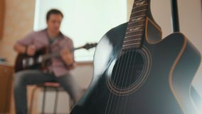 Ο νέος ελκυστικός μουσικός ατόμων συνθέτει τη μουσική στην κιθάρα και τα παιχνίδια, άλλο μουσικό όργανο στο πρώτο πλάνο απόθεμα βίντεο