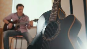 Ο νέος ελκυστικός μουσικός συνθέτει τη μουσική στην κιθάρα και τα παιχνίδια, άλλο μουσικό όργανο στο πρώτο πλάνο, που θολώνεται απόθεμα βίντεο