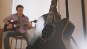Ο νέος ελκυστικός μουσικός συνθέτει τη μουσική στην κιθάρα και τα παιχνίδια, άλλο μουσικό όργανο στο πρώτο πλάνο, που θολώνεται στοκ φωτογραφία με δικαίωμα ελεύθερης χρήσης