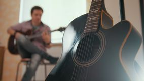 Ο νέος ελκυστικός μουσικός τύπων συνθέτει τη μουσική στην κιθάρα και τα παιχνίδια, άλλο μουσικό όργανο στο πρώτο πλάνο απόθεμα βίντεο