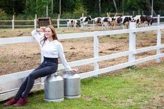 Ο νέος ενήλικος αγρότης κοριτσιών ευτυχίας, που κάθεται στο γάλα μπορεί μετά από την εργασία Στοκ Εικόνες