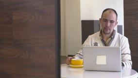 Ο νέος επαγγελματίας πίνει τον καφέ στον πίνακα με το lap-top στο σύγχρονο γραφείο φιλμ μικρού μήκους