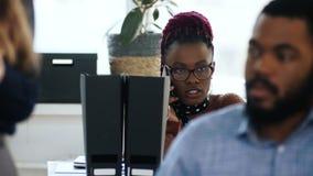 Ο νέος επαγγελματικός αφρικανικός θηλυκός προϊστάμενος τονίζεται μιλώντας στην τηλεφωνική συνεδρίαση στον πίνακα στο multiethnic  φιλμ μικρού μήκους