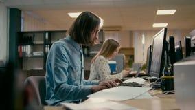 Ο νέος επαγγελματικός σχεδιαστής εργάζεται στον υπολογιστή στο γραφείο με την ομάδα απόθεμα βίντεο