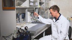 Ο νέος επιστήμονας πραγματοποιεί τα χημικά πειράματα με τα υγρά στο εργαστήριο απόθεμα βίντεο