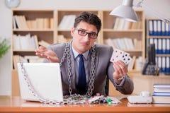 Ο νέος επιχειρηματίας έθισε στις σε απευθείας σύνδεση κάρτες παιχνιδιού παίζοντας στο τ Στοκ Εικόνες