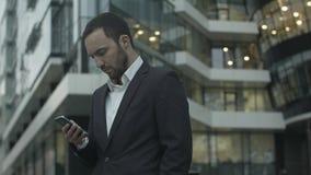 Ο νέος επιχειρηματίας διαβάζει ένα μήνυμα κειμένου που στέκεται έξω από το γραφείο στοκ φωτογραφίες