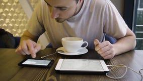 Ο νέος επιχειρηματίας εξετάζει το crypto-νόμισμα σειρών μαθημάτων σε έναν καφέ φιλμ μικρού μήκους