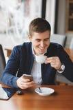 Ο νέος επιχειρηματίας διαβάζει SMS στο τηλέφωνο στον καφέ Στοκ Φωτογραφίες