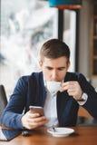 Ο νέος επιχειρηματίας διαβάζει SMS στο τηλέφωνο στον καφέ Στοκ Εικόνες
