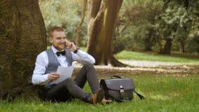 Ο νέος επιχειρηματίας κάθεται κάτω από το δέντρο απόθεμα βίντεο