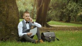 Ο νέος επιχειρηματίας κάθεται κάτω από το δέντρο φιλμ μικρού μήκους