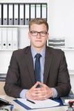 Ο νέος επιχειρηματίας κάθεται στο γραφείο στο γραφείο Στοκ Εικόνες