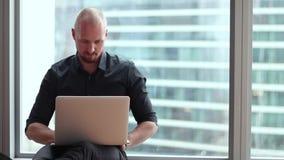 Ο νέος επιχειρηματίας κάθεται στο πάτωμα στο γραφείο με ένα lap-top απόθεμα βίντεο