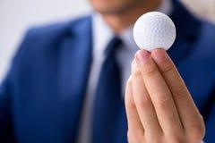 Ο νέος επιχειρηματίας με την εργασία σφαιρών γκολφ στην αρχή Στοκ Εικόνα