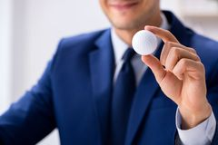 Ο νέος επιχειρηματίας με την εργασία σφαιρών γκολφ στην αρχή Στοκ Εικόνες