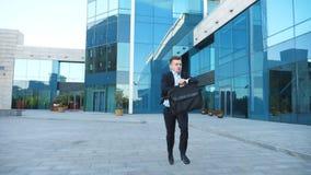 Ο νέος επιχειρηματίας με το χαρτοφύλακα τρέχει και εξετάζει το ρολόι του Βέβαιος τύπος αργά για τη συνεδρίαση Επιτυχές άτομο στο  φιλμ μικρού μήκους