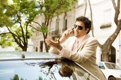 Επιχειρηματίας που κλίνει στο αυτοκίνητο. Στοκ Φωτογραφίες
