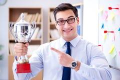 Ο νέος επιχειρηματίας που λαμβάνει το φλυτζάνι βραβείων στην αρχή Στοκ Φωτογραφία