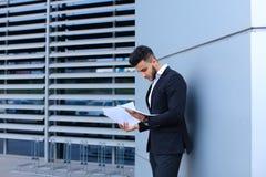 Ο νέος επιχειρηματίας που ο ασιατικός τύπος κρατά και εξετάζει, διαβάζει και ταξινομεί Στοκ εικόνα με δικαίωμα ελεύθερης χρήσης