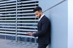Ο νέος επιχειρηματίας που ο ασιατικός τύπος κρατά και εξετάζει, διαβάζει και ταξινομεί Στοκ Φωτογραφία
