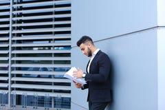 Ο νέος επιχειρηματίας που ο ασιατικός τύπος κρατά και εξετάζει, διαβάζει και ταξινομεί Στοκ φωτογραφίες με δικαίωμα ελεύθερης χρήσης