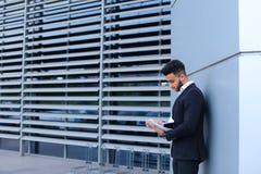 Ο νέος επιχειρηματίας που ο ασιατικός τύπος κρατά και εξετάζει, διαβάζει και ταξινομεί Στοκ εικόνες με δικαίωμα ελεύθερης χρήσης