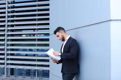 Ο νέος επιχειρηματίας που ο ασιατικός τύπος κρατά και εξετάζει, διαβάζει και ταξινομεί Στοκ Εικόνα