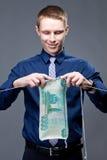 Ο νέος επιχειρηματίας πλέκει ένα τραπεζογραμμάτιο δολαρίων Στοκ Εικόνες