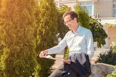 Ο νέος επιχειρηματίας στα γυαλιά διαβάζει τα έγγραφα και χαμογελά στην οδό ο τύπος κρατά το σακάκι στα χέρια του στοκ φωτογραφίες με δικαίωμα ελεύθερης χρήσης