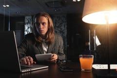 Ο νέος επιχειρηματίας hipster κάθεται από τον ξύλινο πίνακα με το γραφείο λαμπτήρων, lap-top και smartphone τη νύχτα Άτομο με τη  Στοκ Εικόνες