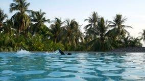 Ο νέος ευτυχής αθλητής κολυμπά στην πισίνα κατά τη διάρκεια των διακοπών θερινών διακοπών θερινή περίοδο στην τροπική έννοια περι φιλμ μικρού μήκους
