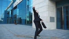 Ο νέος ευτυχής επιχειρηματίας στο κοστούμι χαίρεται για την καλή διαπραγμάτευση στην οδό πόλεων Ο επιτυχής εργαζόμενος γραφείων μ φιλμ μικρού μήκους